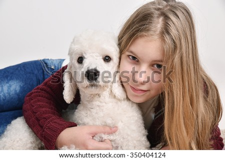 Studio portrait of a beautiful teenage girl Holding her pet poodle