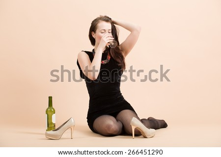 Studio portrait of a beautiful young brunette woman holding a glass of white wine - stock photo