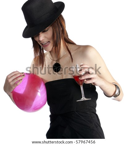 Studio portrait of a beautiful young female model holding a pink balloon, wearing a black top and hat holding a glass of wine, isolated on a white background. - stock photo