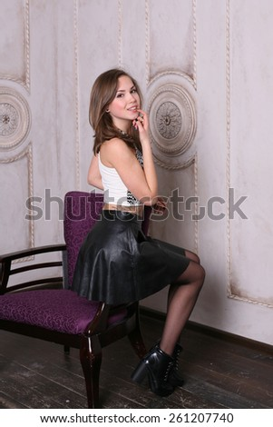Studio portrait of a beautiful young girl with a chair - stock photo