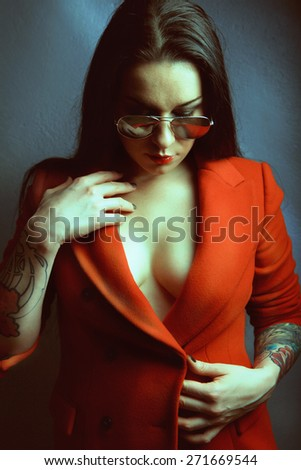 Studio portrait of a beautiful young woman in red coat, - stock photo