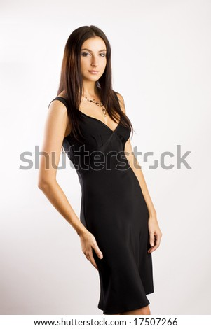 Studio portrait of a beautiful young woman sexy in black dress, gray background - stock photo
