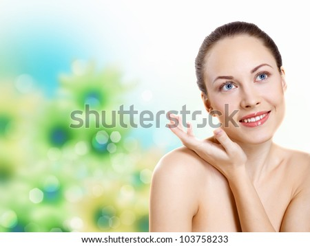Studio portrait of a beautiful young woman with flowers on background