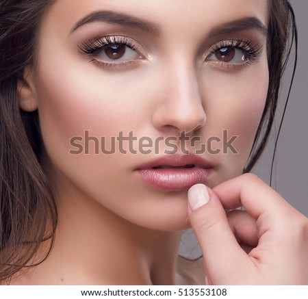 Studio portrait of a beautiful young woman with natural make-up and wet brown hair. Long lashes, full glossy lips, mascara extensions. Skincare, cosmetics. Glamorous fashion beauty look