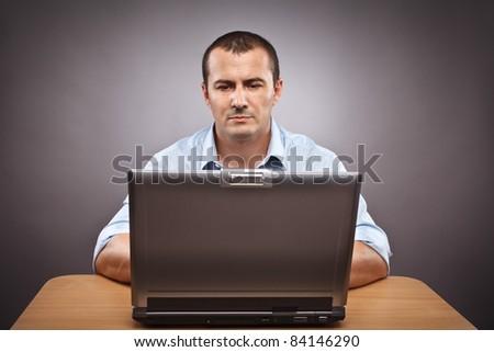 Studio portrait of a businessman at his laptop - stock photo