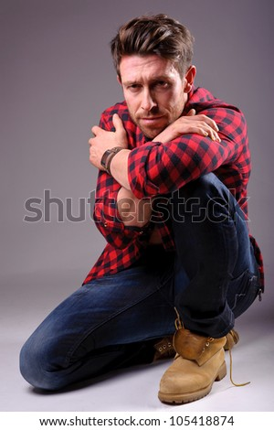 studio portrait of a calm handsome man in jeans and red and black shirt - stock photo
