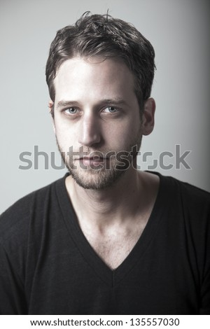 Studio portrait of a caucasian adult man in his early 30's over gray background. He's looking at the camera with a serious enigmatic expression, piercing the lens with his grayish blue eyes. - stock photo