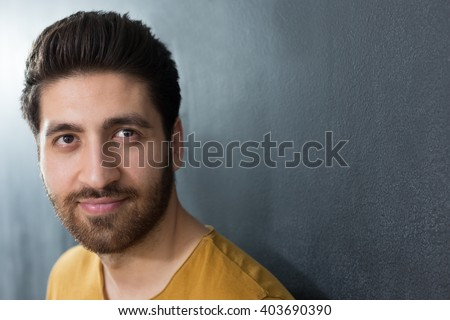 Studio portrait of a caucasian adult man in his early 30's over gray background. He seems to be in a good mood, looking at the camera with a large toothy smile on his face - stock photo