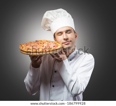 Studio portrait of a chef with closed eyes smelling pizza - stock photo