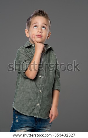 Studio portrait of a child thinking, gray background