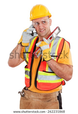 Studio portrait of a construction worker wearing safety gear a work belt and holding a level while talking on a cell phone isolated on white.