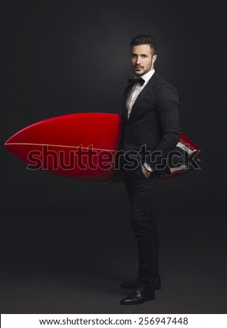 Studio portrait of a fashion young man wearing a suit and posing with a surfboard - stock photo