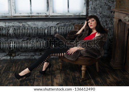 Studio portrait of a fashionable woman resting in a vintage room - stock photo