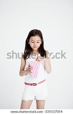 Studio portrait of a girl eating popcorn - stock photo
