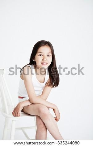 Studio portrait of a girl. Light background - stock photo