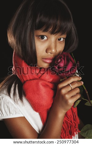 Studio portrait of a girl of Asian ethnicity in a red scarf with burgundy rose in her hand. Beautiful tan chocolate brow - stock photo