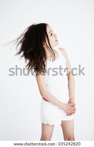 Studio portrait of a girl standing. Light background - stock photo