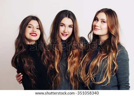 Studio portrait of a group of three young beautiful model smiling and having fun. Consumer concept, winter fashion, attractive young women - stock photo