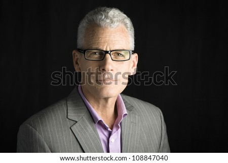 Studio Portrait of a handsome businessman wearing glasses looking to the camera - stock photo