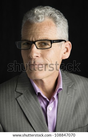 Studio Portrait of a handsome businessman wearing glasses looking to the camera