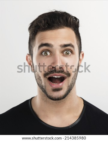 Studio portrait of a handsome young man astonished and happy expression - stock photo