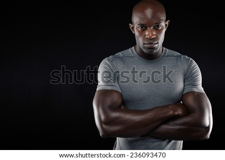 Studio portrait of a handsome young man in sportswear with his arms crossed standing against black background with copy space. Muscular african sportsman. - stock photo
