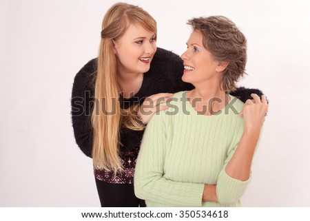 Studio portrait of a happy grandmother and granddaughter with lush curves isolated on white