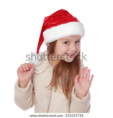Studio portrait of a happy surprised little girl with long hair in red Santa hat on white background/Image of lovely child in a Santa hat is happy and laughs - stock photo