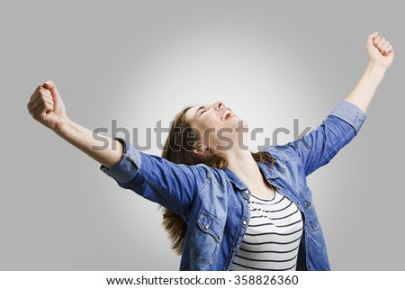 Studio portrait of a happy woman with arms raised - stock photo