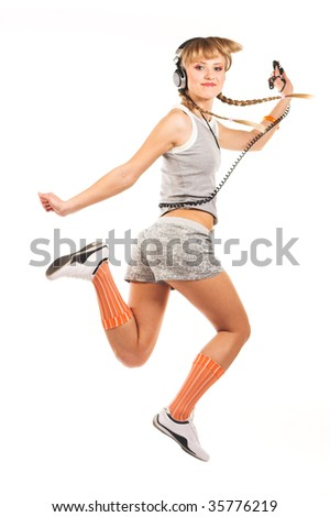 Studio portrait of a jumping girl in headphones isolated on white background