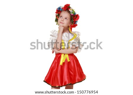 Studio portrait of a little girl in Ukrainian national costume dances beautifully on Holiday