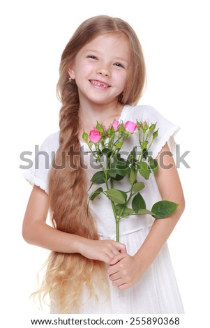 Studio portrait of a little girl with long healthy hair holding a bouquet of delicate pink roses on Holiday - stock photo