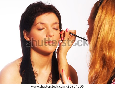 Studio portrait of a makeup artist at work isolated on white background