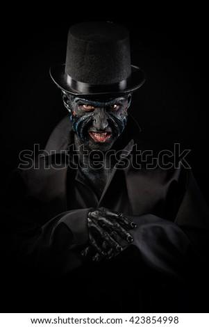 Studio portrait of a man in monster makeup, dark background - stock photo