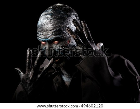 Studio portrait of a man in monster makeup, dark background