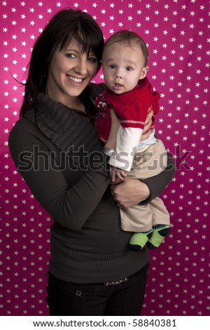 Studio portrait of a mother holding her beautiful baby boy in front of a ping background with star shapes. - stock photo