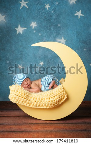 Studio portrait of a nine day old baby boy wearing pajama bottoms and a sleeping cap. He is sleeping on a moon shaped posing prop. - stock photo