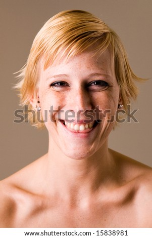 Studio portrait of a short haired blond girl clearly having fun
