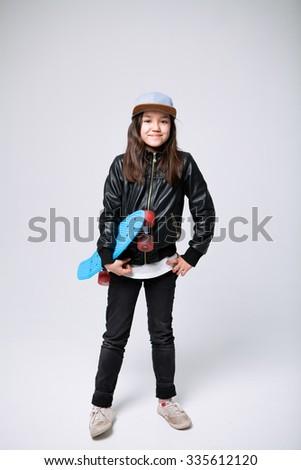 Studio portrait of a skateboarder girl - stock photo
