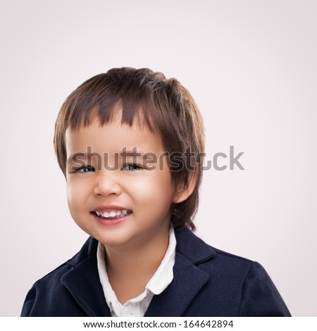 Studio portrait of a smiling Asian boy.