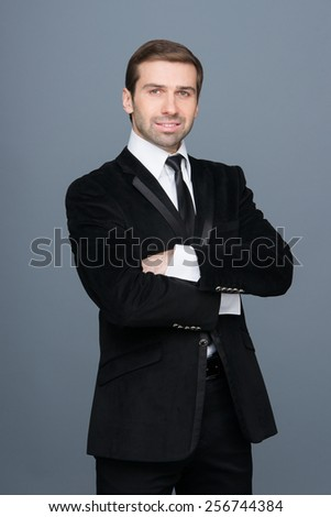 Studio portrait of a smiling fashion young businessman, arms folded. - stock photo