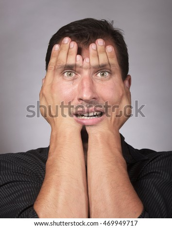 Studio portrait of a stressed Caucasian man covering his face with the hands
