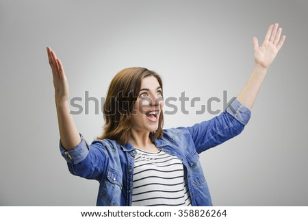 Studio portrait of a successful woman with arms raised - stock photo