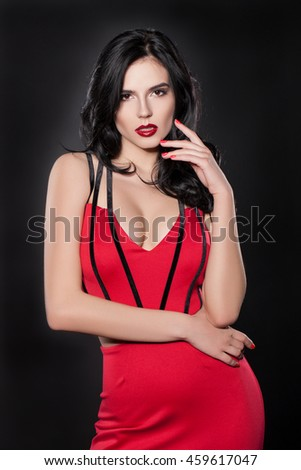 Studio portrait of a woman. Beautiful woman in a red dress on a black background. ATTRACTIVE stylish woman in fashion clothes. Brunette woman with red lips. charming woman looking at the camera