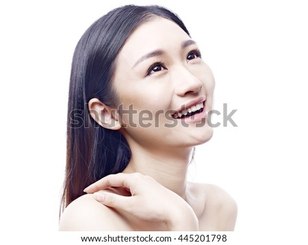 studio portrait of a young and beautiful asian model, long hair, looking up and smiling, isolated on white background. - stock photo