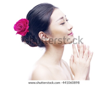 studio portrait of a young asian woman, eyes closed, side view, isolated on white. - stock photo