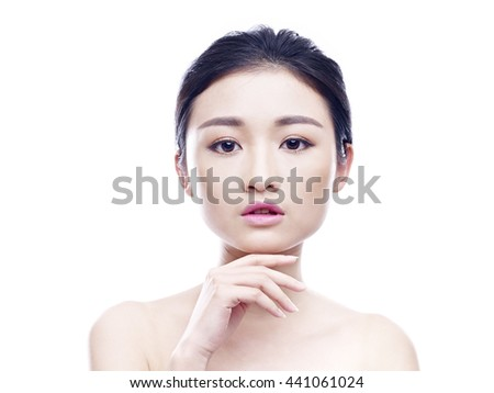 studio portrait of a young asian woman, looking at camera, hand on chin, frontal view, isolated on white. - stock photo