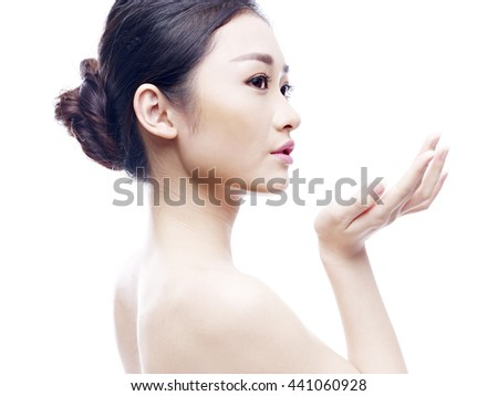 studio portrait of a young asian woman, side view, isolated on white. - stock photo