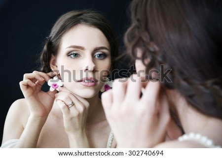 Studio portrait of a young beautiful bride looking in the mirror in a white dress. Professional make-up and hairstyle. Black background - stock photo