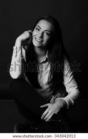 Studio portrait of a young beautiful girl business student wearing shirt in black and white on black background